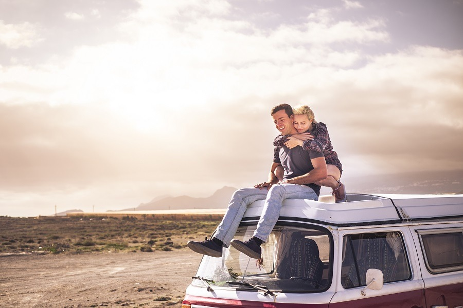 Young couple in love enjoying the travel on a vintage van during a golden sunset.