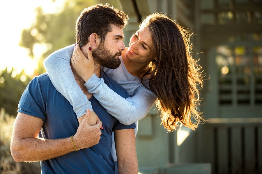 Handsome bearded man and brunette woman, strong athletic lovers embrace at the park.