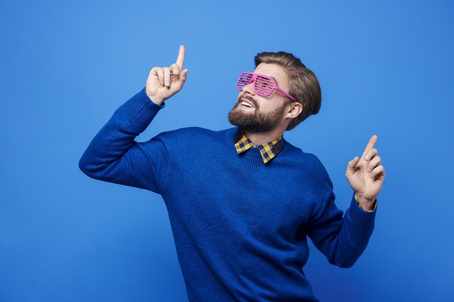 Man in blue sweater with sunglasses in acting pose.