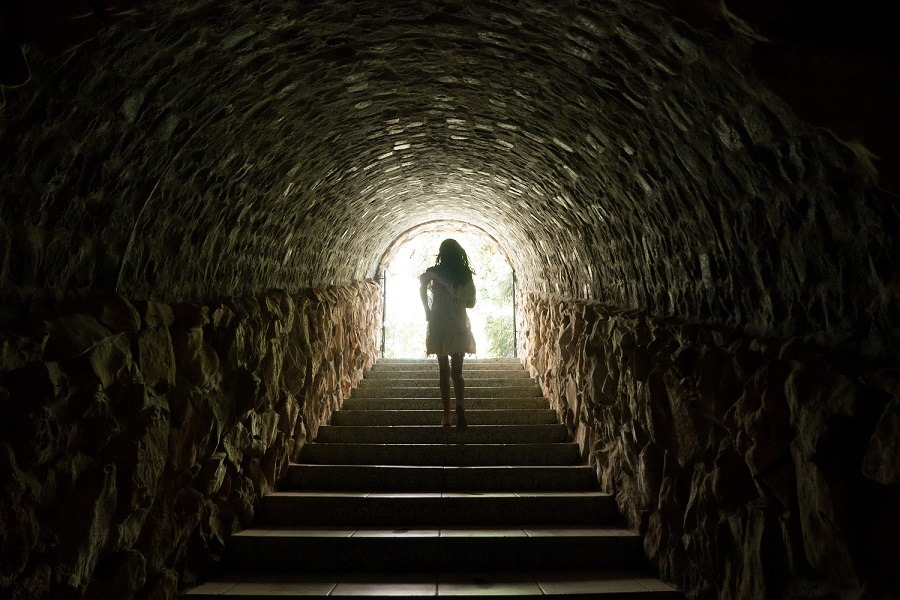 Girl running towards the light at the end of the dark tunnel.