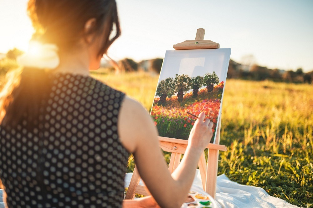 A girl painting outdoors on canvas at sunset.