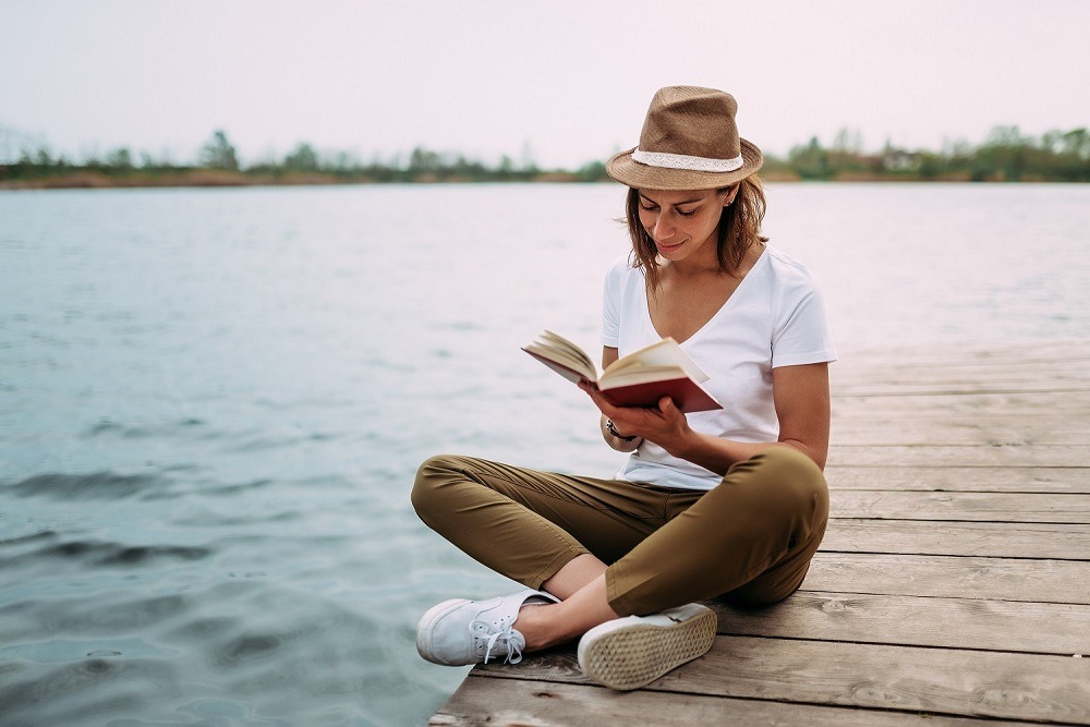 A girl reading while sitting on wooden lake plank.