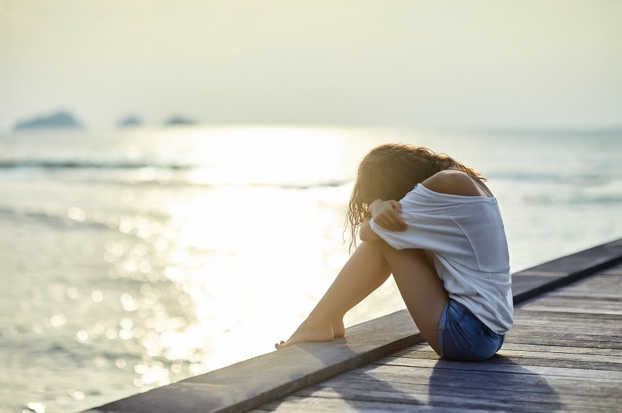 Sad lonely woman sitting on wooden dock, head tucked crying.