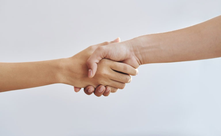 Close-up image of man and woman shaking hands