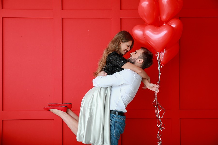 Happy young couple with heart-shaped balloons on color background.