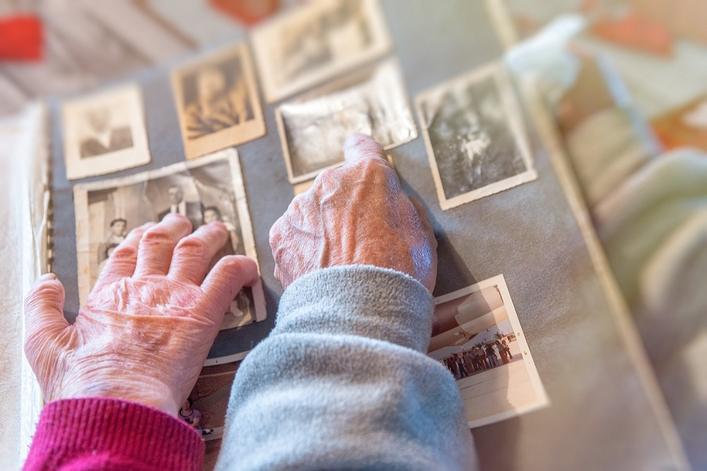 Elderly couple hands touching at old pictures album at home.