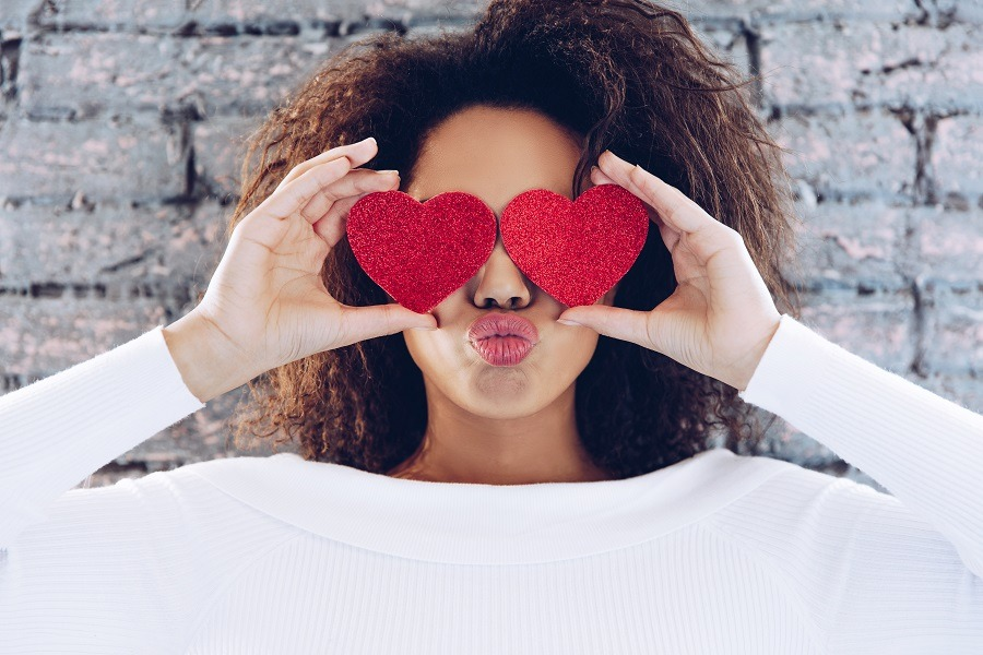 Happy lady holding hearts covering her eyes, lips pouting.