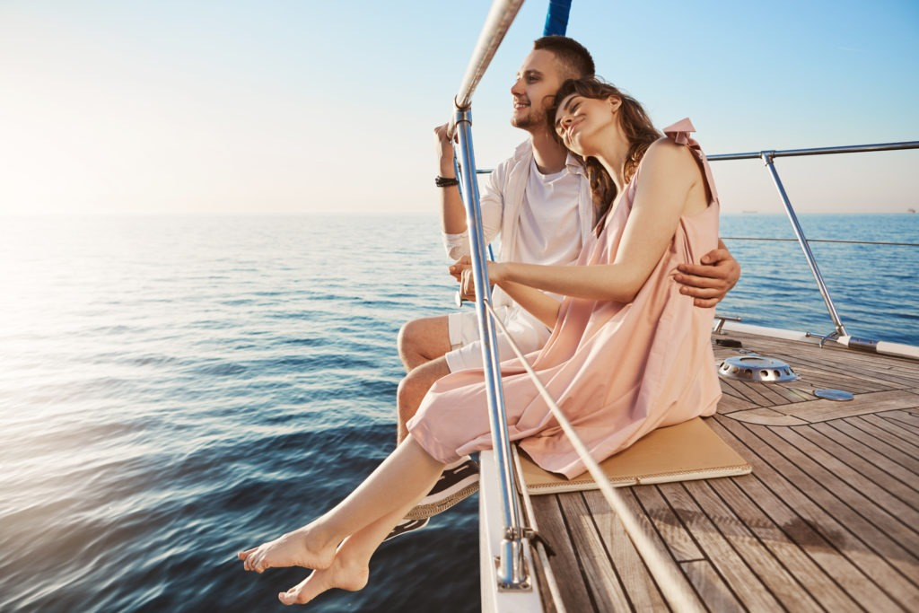 Happy beautiful couple sitting on side of yacht