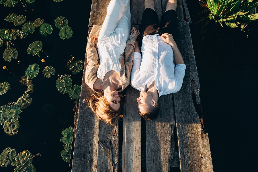 Beautiful young couple lies on a wooden bridge on the lake, looks lovingly at each other and smiles.
