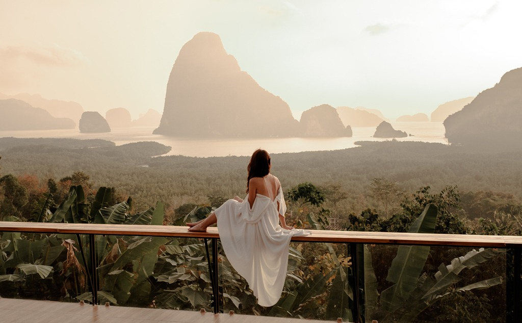 Woman with the white dress sit and watching the mountain