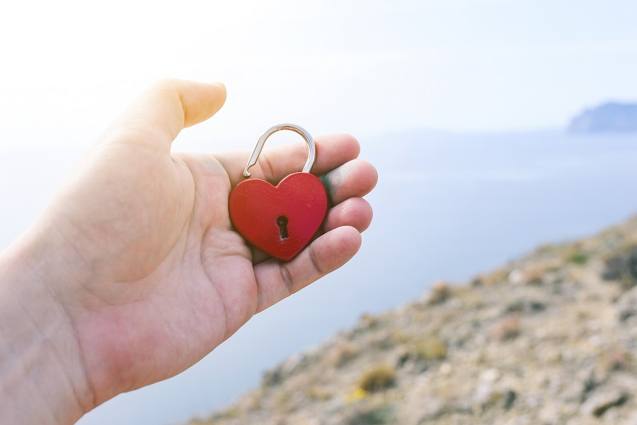 Male hand holding a heart lock with the sea in the background.