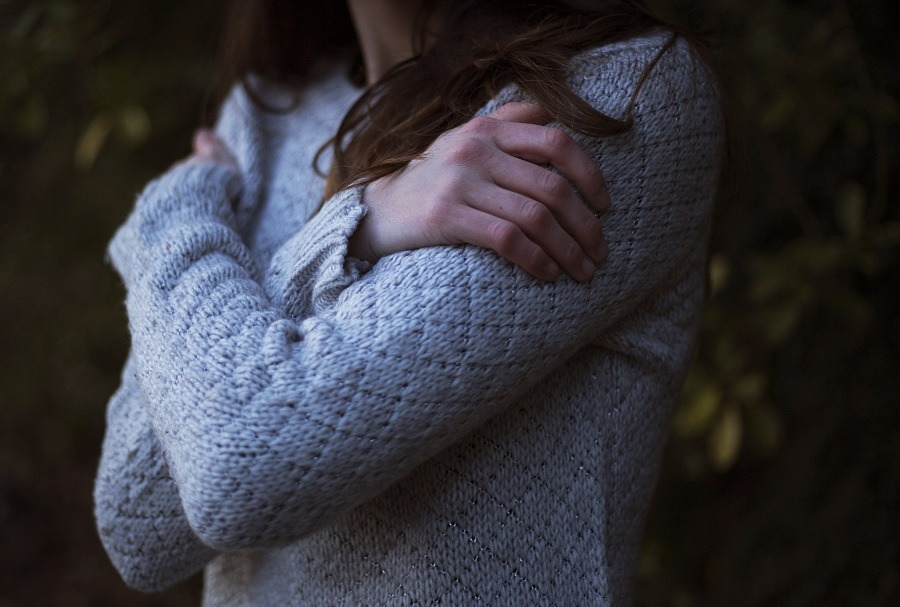 A young woman hugging herself arms crossed on her chest as if in emotional pain.