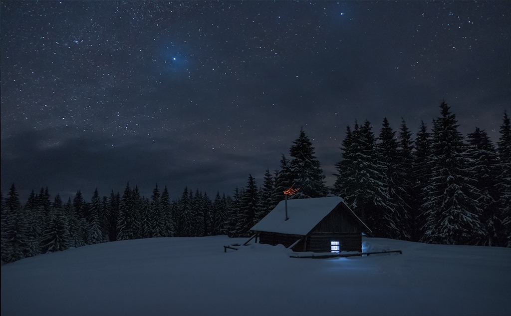 Wooden cabin under stars. Lights shines through the window from