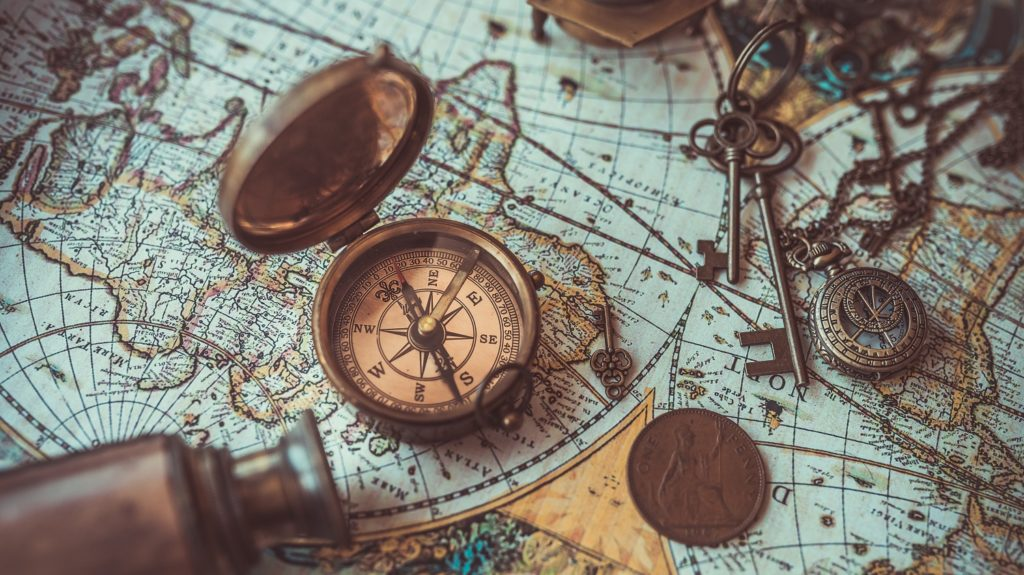 A vintage compass and telescope on top of an antique world map.