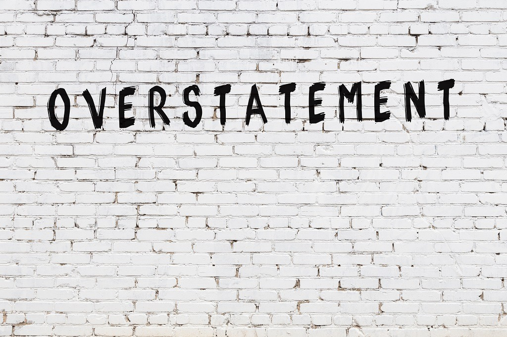 Word overstatement painted on white brick wall.