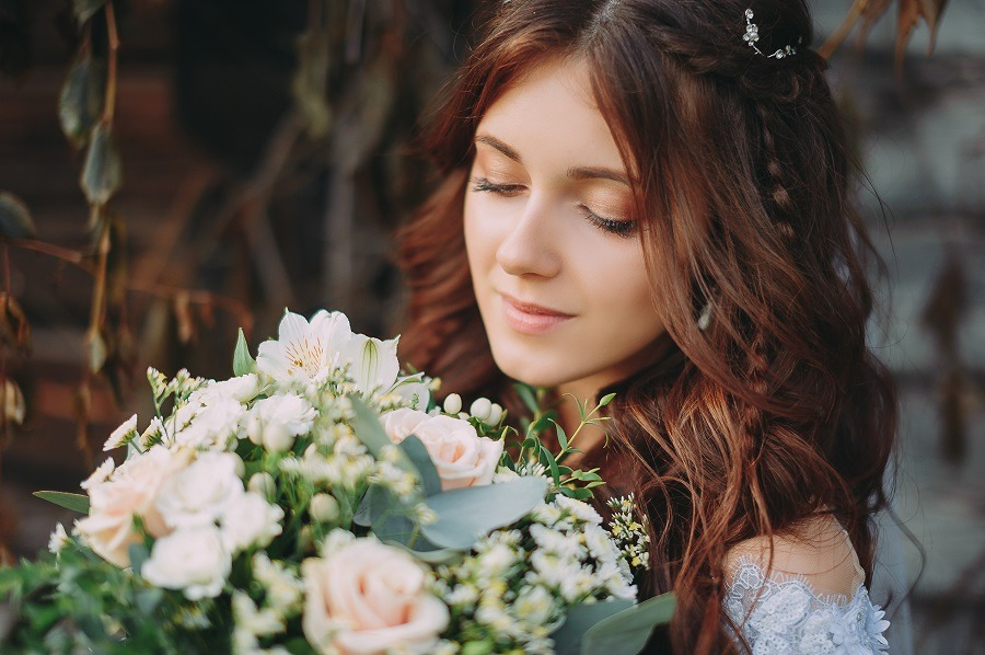 Face of a beautiful bride with fresh wedding bouquet.