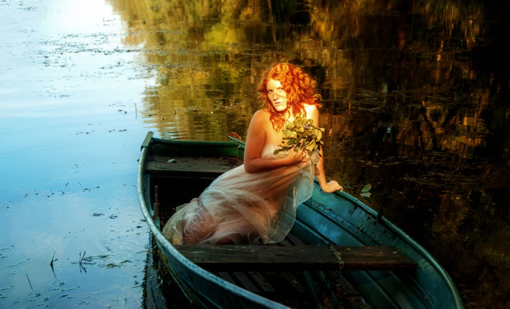A young sexy red-haired woman sits in a boat like a siren in an old pre-Raphaelite painting.