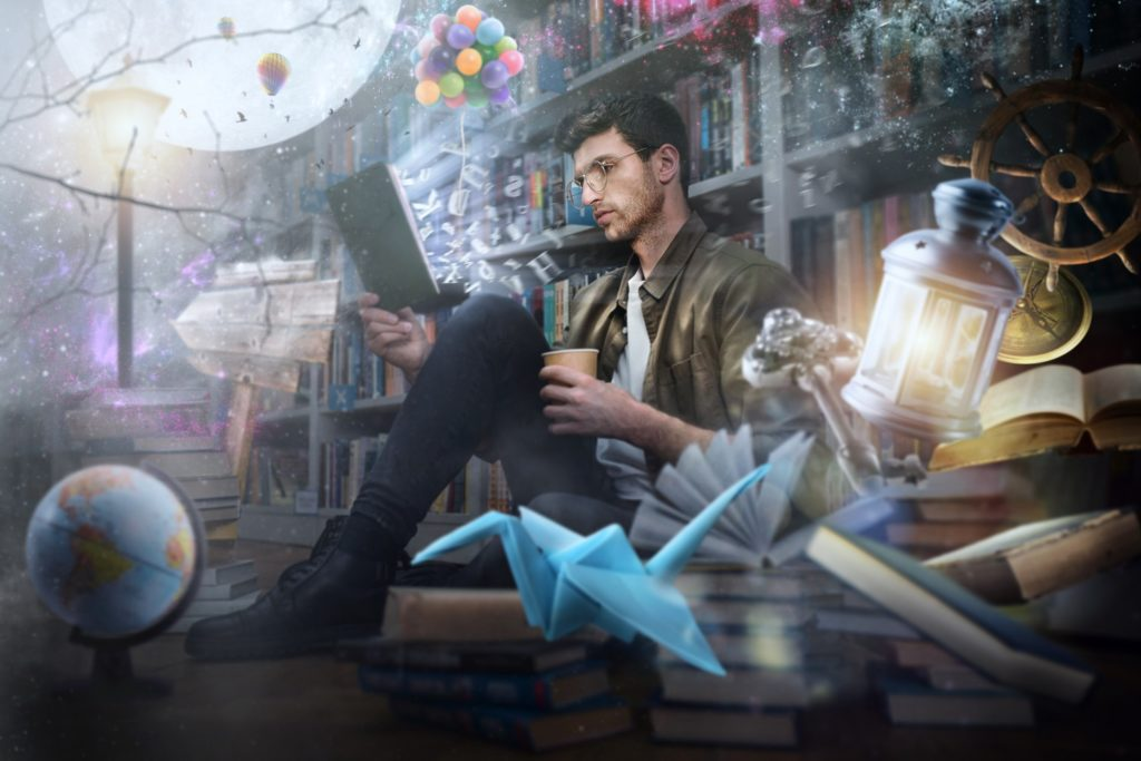 A man reading a book with graphic images of his imaginations floating in the background.