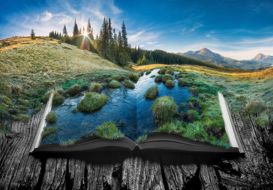 Picturesque life-like view of alpine mountain valley on the pages of an open book.