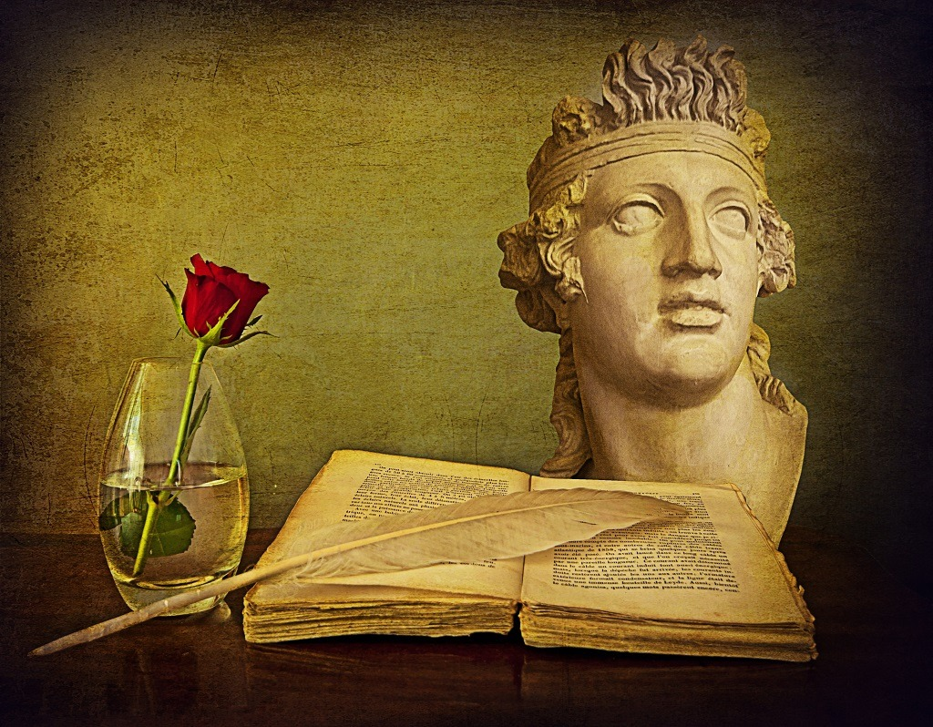 Antique Greek poetry book with quill next to a vase with a red rose.