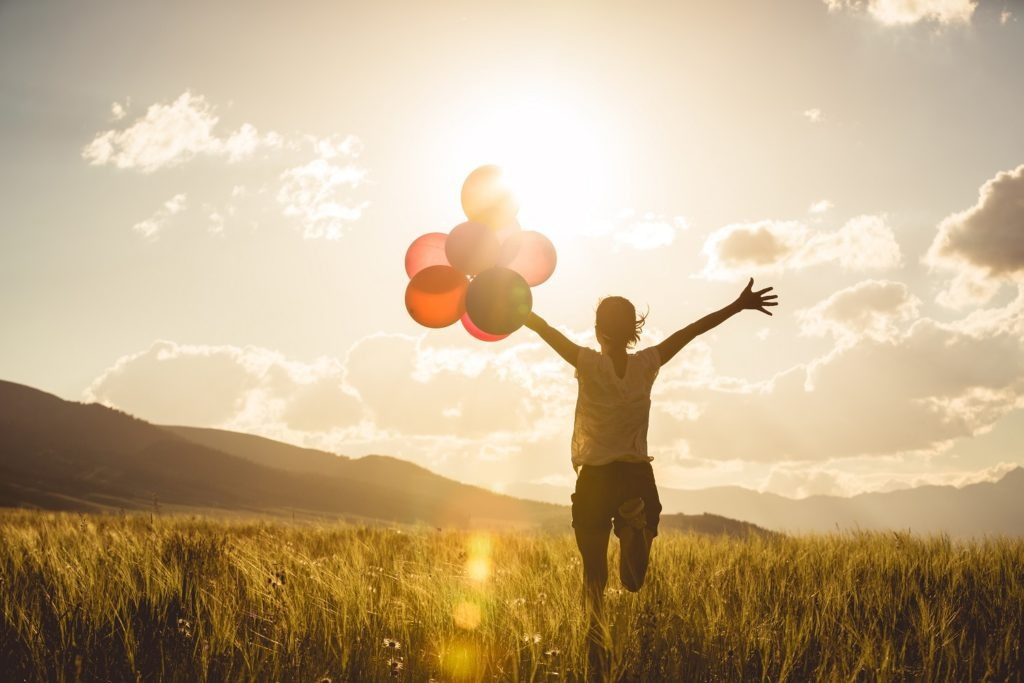 Young woman on grassland, arms outstretched with left hand holding balloons.