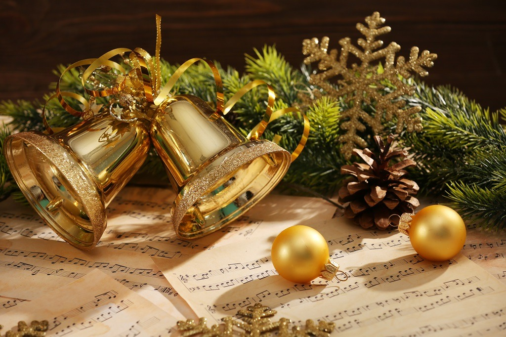 Golden Christmas bells and balls on music sheets.