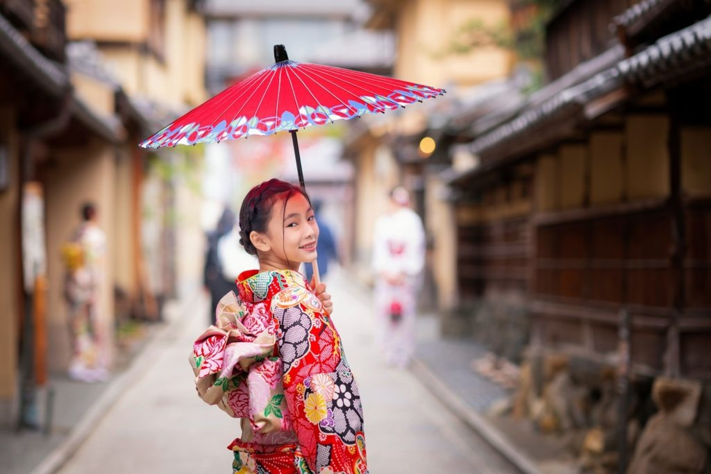 A Japanese girl in a red kimono with a matching parasol, walking to the market.
