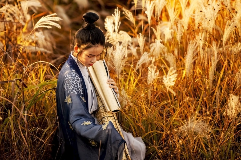 Asian Chinese Tang Dynasty woman with an ancient book enjoying the sun outdoors.