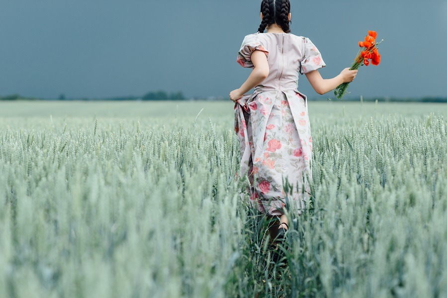 A young pretty girl running on the field with green wheat.