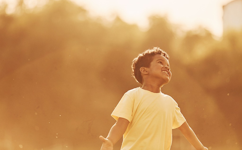 Beautiful sunshine. african american kid have fun in the field at summer daytime