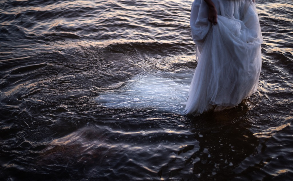 Woman standing in the sunset sea waves i