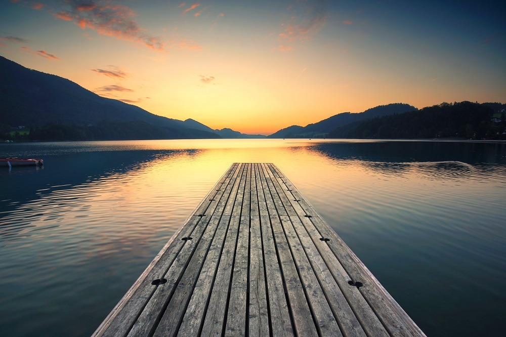 Peaceful view of the lake on a jetty at sunrise.