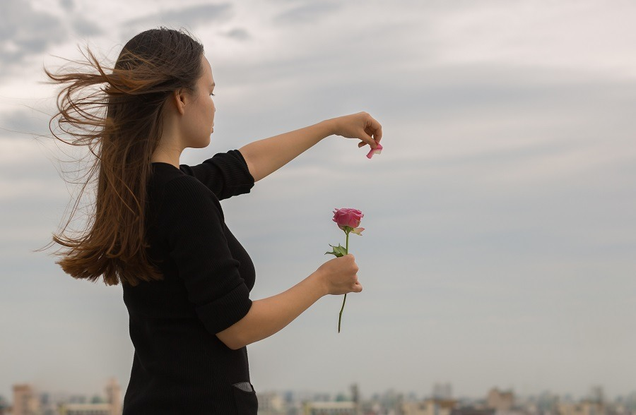 Young girl in black plucks petals from a rose lets them go into the air.