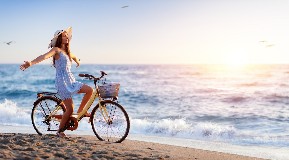 Young woman biking on the beach, arms outstretched.
