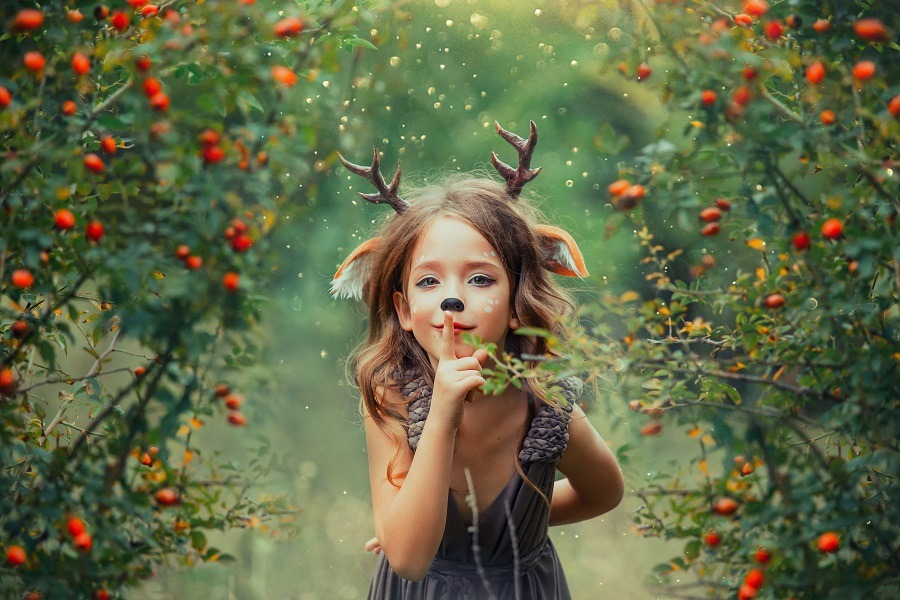 Little fawn in a barberry and dog rose grove, plays hide-and-seek and holds a finger to lips, a light brown dress with purple tint.