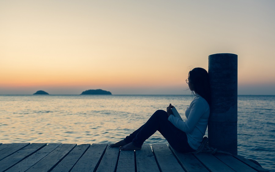 Lonely woman sitting on a wooden bridge at sunset.