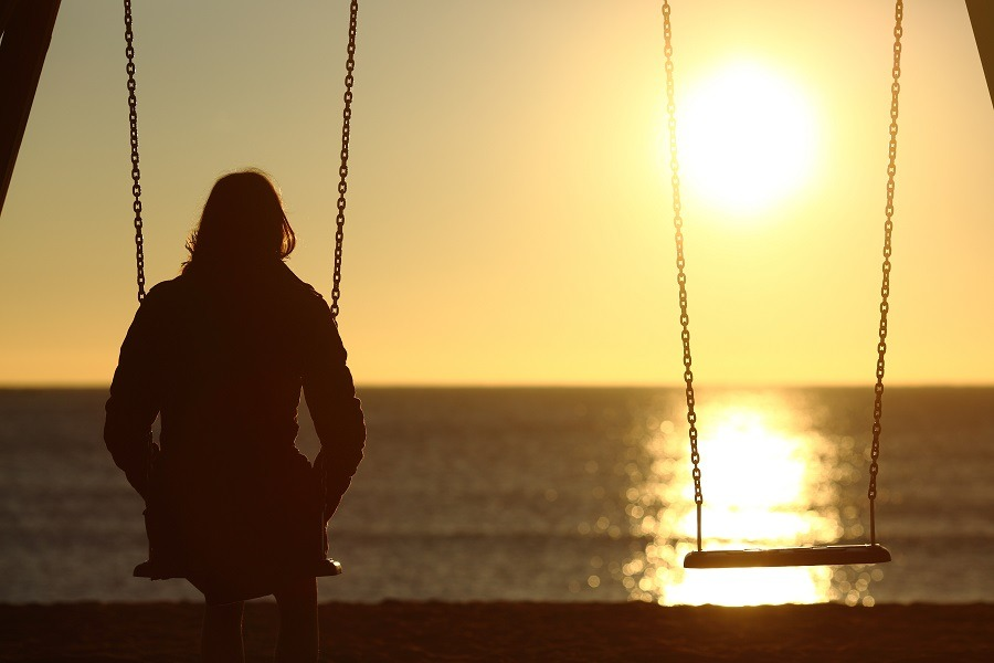 Lonely woman sitting on a swing, watching the sunset alone.