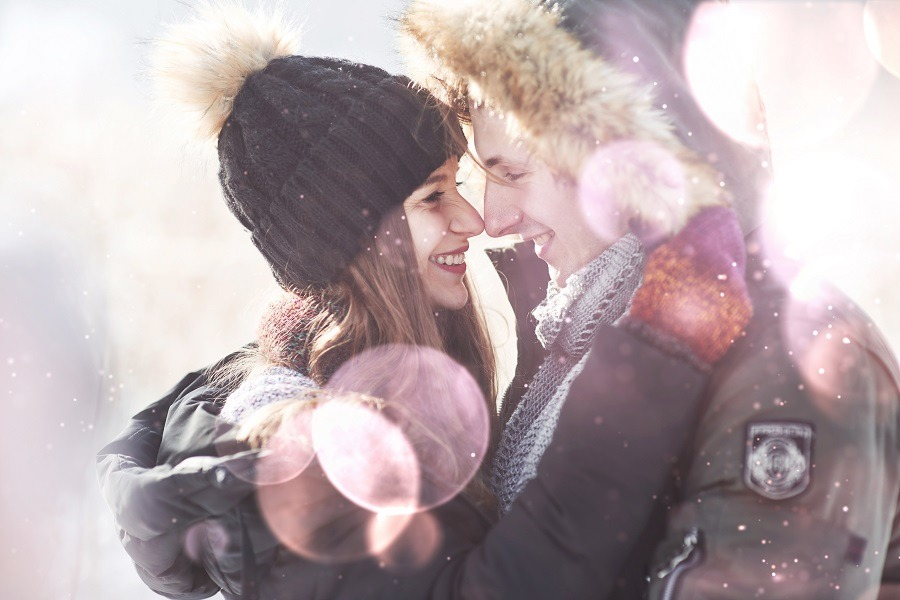 Young happy couple in love embrace in snowy winter cold forest.