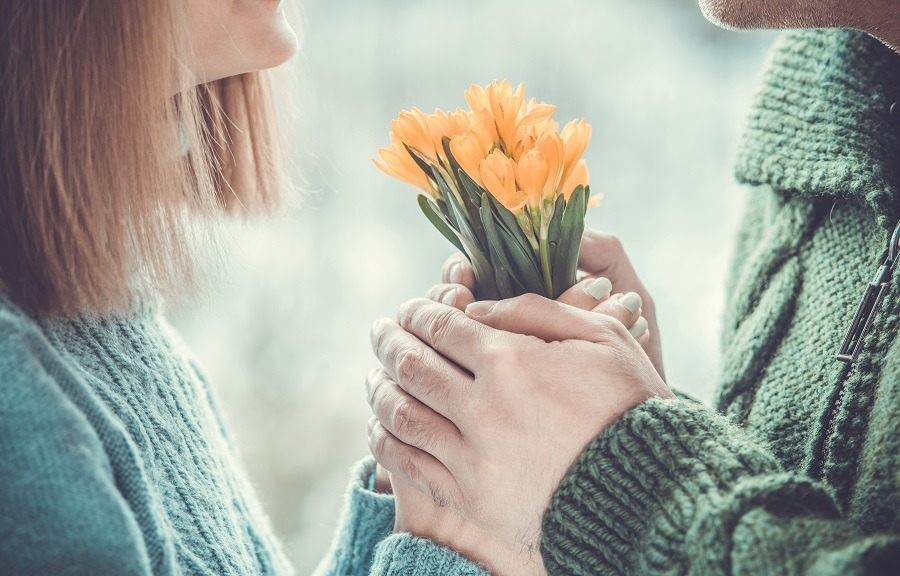 Loving couple holding hands each other with bouquet of beautiful yellow flowers.