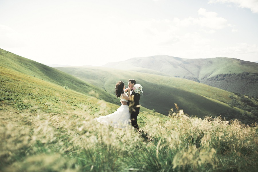 Beautiful wedding couple in love on green rolling hills.