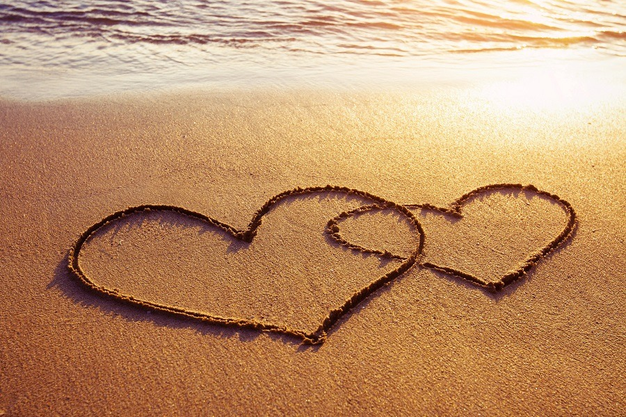 Two intertwined hearts drawn on the beach.