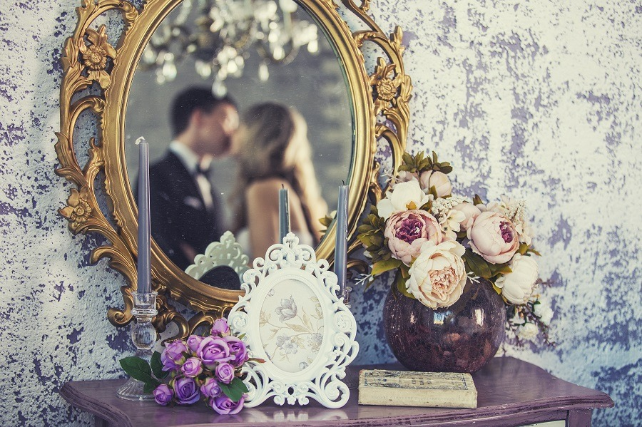 Vintage mirror with kissing bride and groom in the reflection.