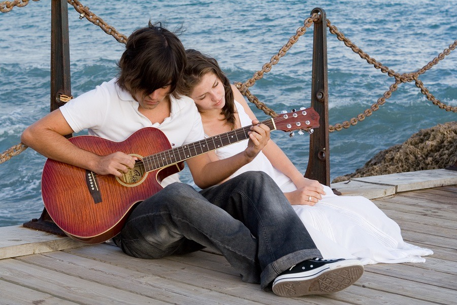 Man playing guitar for her woman by the sea.