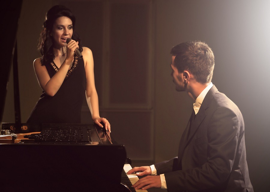 Woman singing man on the piano looking at woman in love.