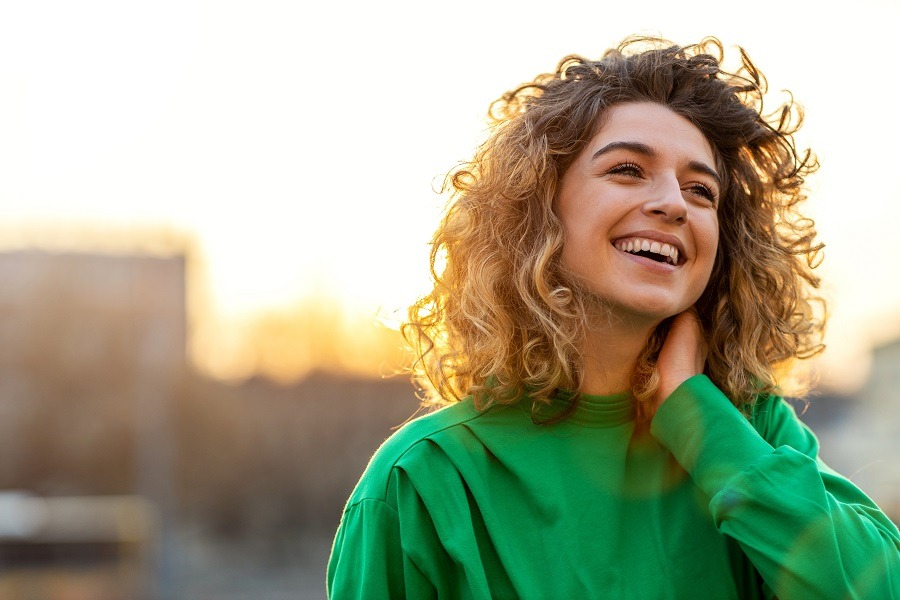 Young happy beautiful lady in the city at sunrise.