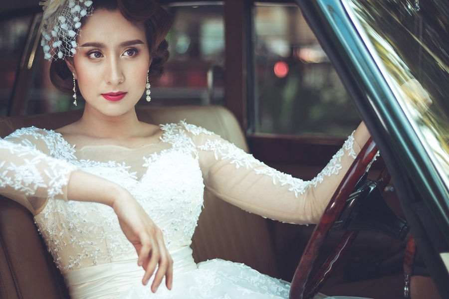 Stunning asian woman wearing a white dress in vintage car.
