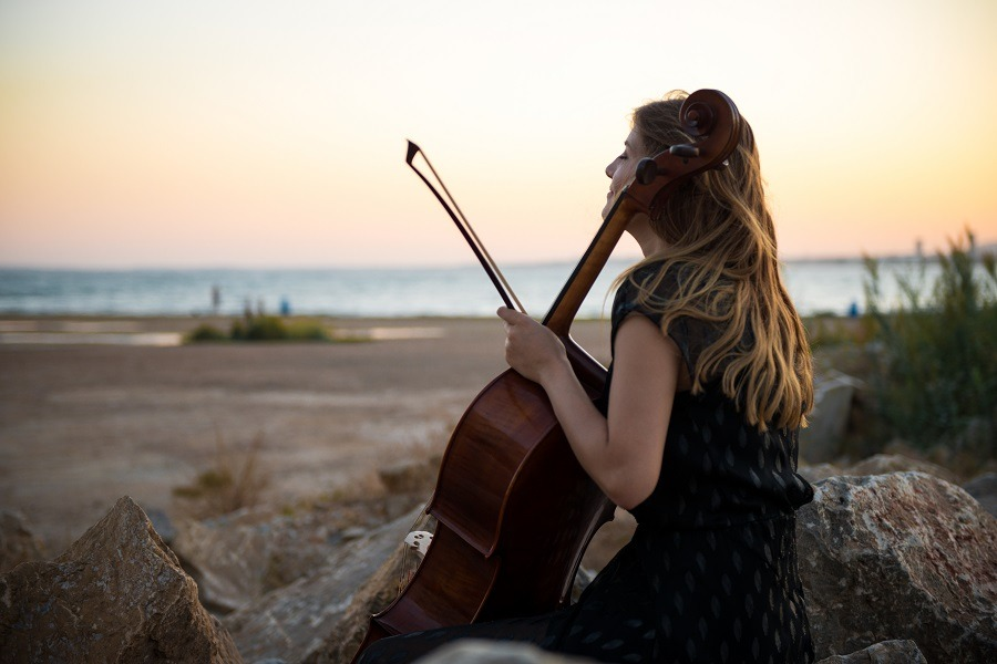 Young beautiful girl with her cello looking dreamily at the ocean.