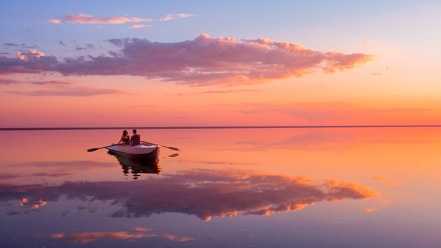 A couple in love look at beautiful sunset in a rowing boat on the lake.