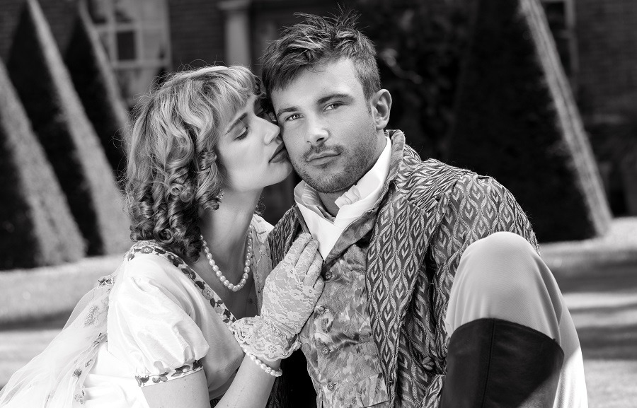 Young lovers dressed in vintage clothing the woman kisses him on cheek.