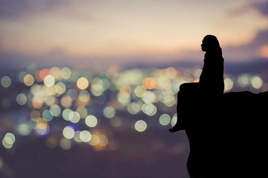 Silhouette of woman sitting alone with blurred view of city lights at night.